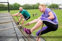 A woman struggles to get to the top of the wall at Muddy Warrior