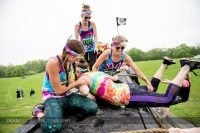 Three women help their teammate at the top of the vertical wall at Muddy Warrior