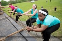 Four women climb the vertical wall at Muddy Warrior