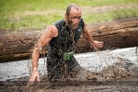 A man comes up out of the ice water during the Muddy Warrior Run