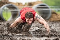 A man crawling through the mud at Muddy Warrior