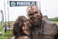With mud all over their faces, a woman kisses her husband