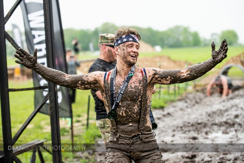 A participant celebrates at the finish line of the Muddy Warrior Run