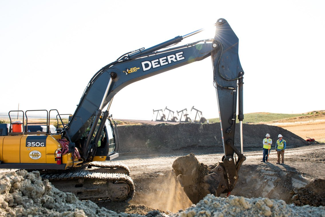 Backhoe digging dirt at oil field in ND