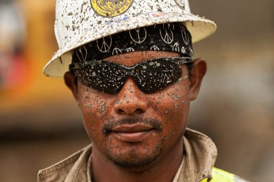The mud covered face of an industrial pipeline worker