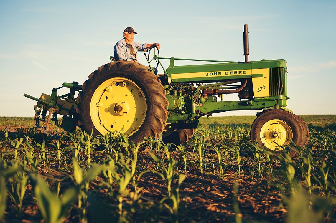 An agricultural portrait of Minnesota farmer on his old John Deere tractor