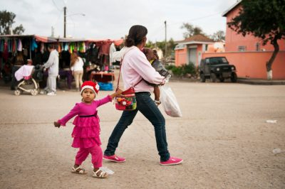 Editorial photography of mother and kids walking down street in Tijuana Mexico
