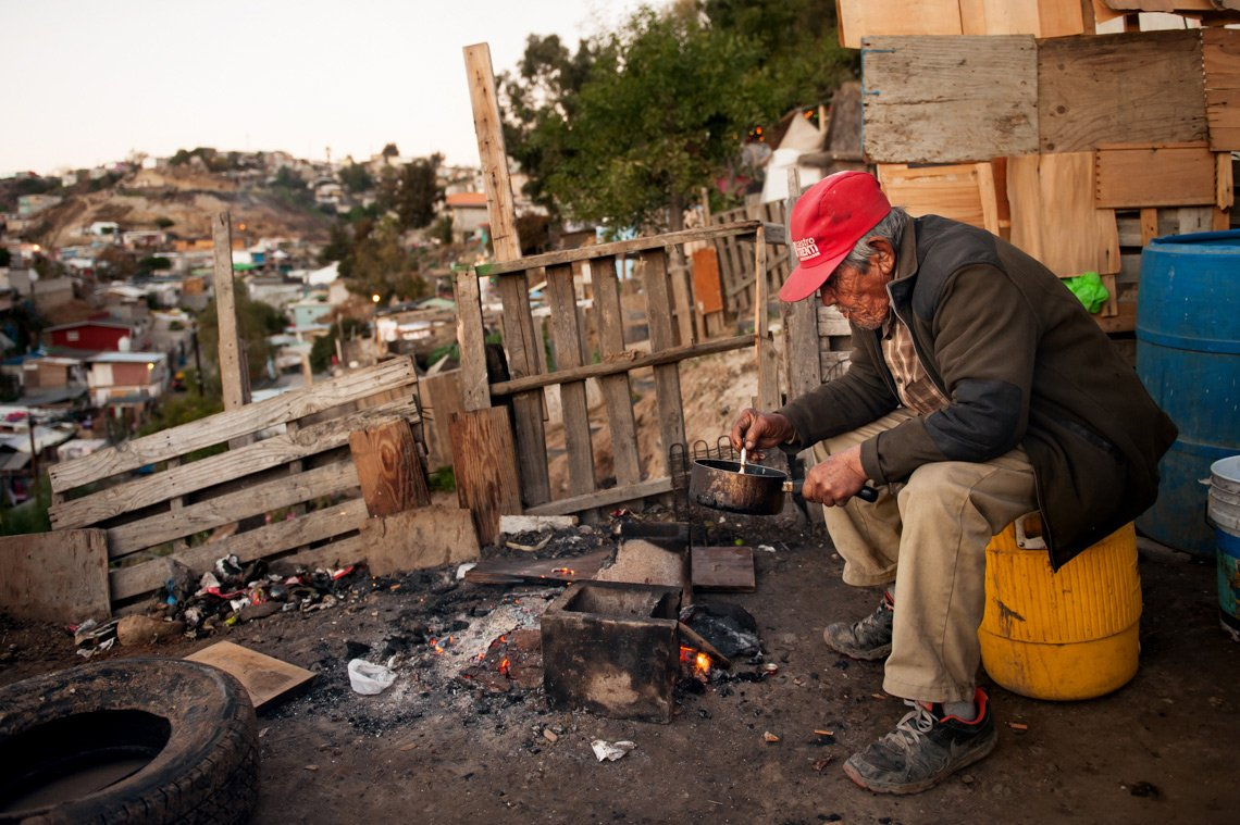 Editorial photography old man eating over fire in Tijuana Mexico