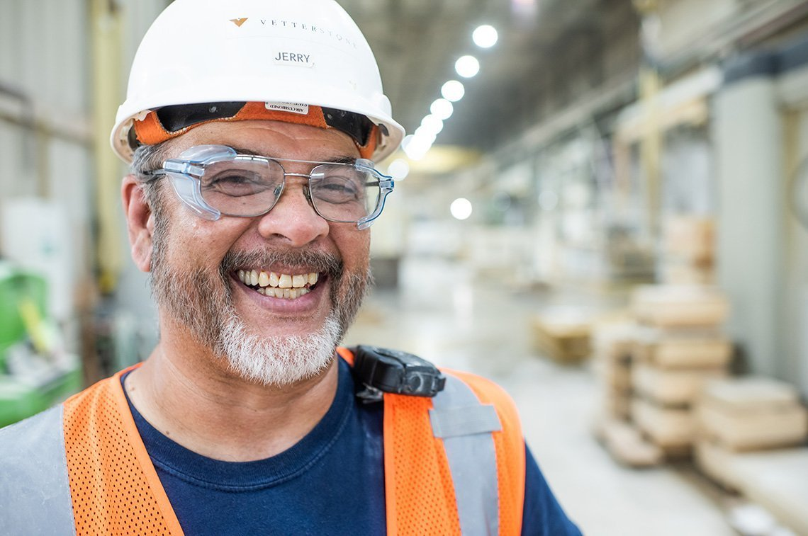 An industrial portrait of worker laughing at Vetter Stone in Minnesota