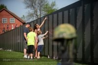 A family of four looks for names on the wall of the traveling Vietnam Veterans Memorial in Albert lea MN