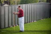 A man leans against his cane as he reads the names on the wall of the traveling Vietnam Veterans Memorial in Albert lea MN