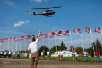 A veteran gives a thumbs up to a Huey helicopter as it lands at the traveling Vietnam Veterans Memorial in Albert lea MN