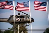Framed with three American flags, a Huey helicopter lands at the traveling Vietnam Veterans Memorial in Albert lea MN
