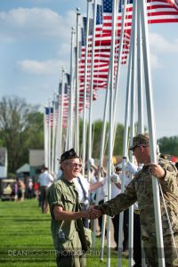 A soldier and a veteran shake hands at the traveling Vietnam Veterans Memorial in Albert lea MN