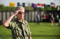 A veteran dressed in fatigues gives a salute at the traveling Vietnam Veterans Memorial in Albert lea MN