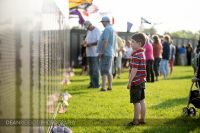 A young boy reads the names on the wall of the traveling Vietnam Veterans Memorial in Albert lea MN