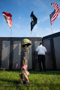 A vet reads the names on the wall of the traveling Vietnam Veterans Memorial in Albert lea MN