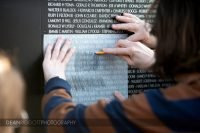 People use thin paper and a mencil to stencil name son the wall of the traveling Vietnam Veterans Memorial in Albert Lean MN