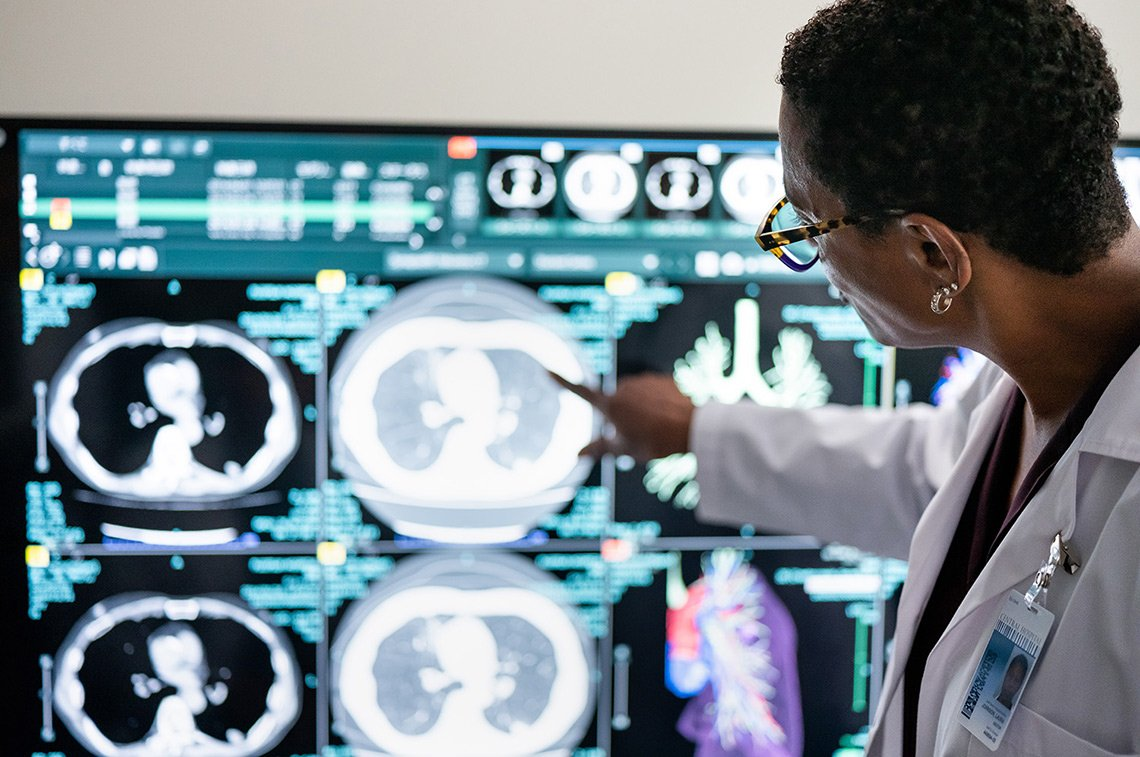A doctor points to something on a monitor for Fujifilm Healthcare