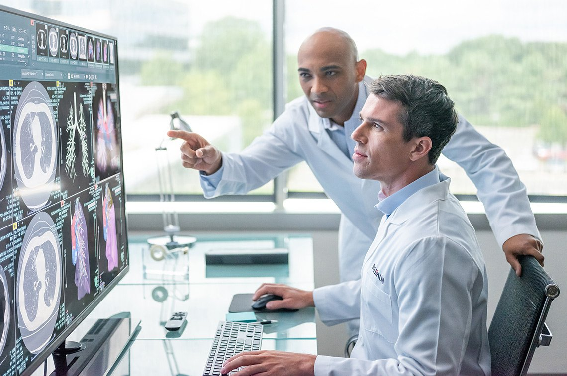 Two doctors look at a large monitor for Fujifilm Healthcare