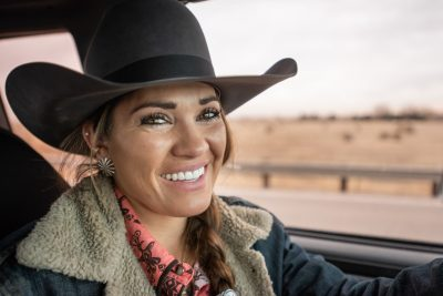 The smiling face of a beautiful cowgirl in her pickup truck
