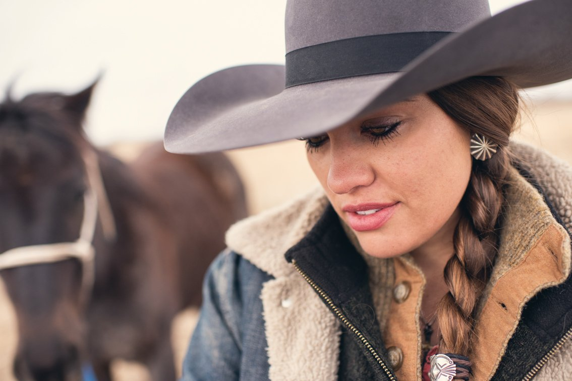 Farm life photo of a cowgirl with her hat and braided hair.
