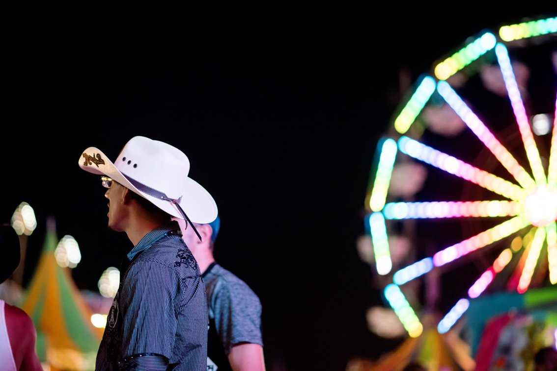 A man in a cowboy hat stands in the midway of the Olmsted County Fair in Minnesta