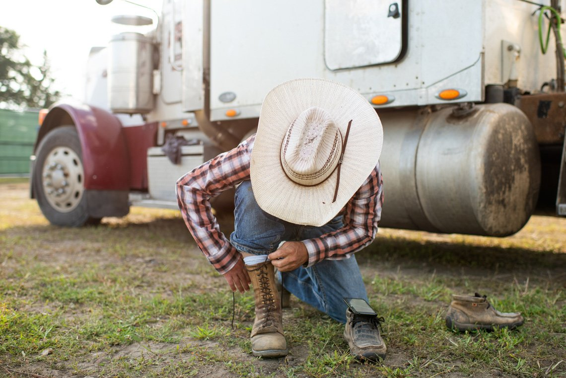 Cowboy lacing his boots at rochester mn rodeo - editorial photo