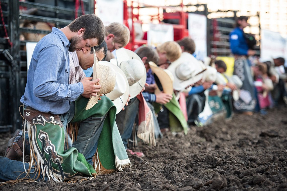 Editorial photo of cowboys kneeling during national anthem at the rochester mn rodeo
