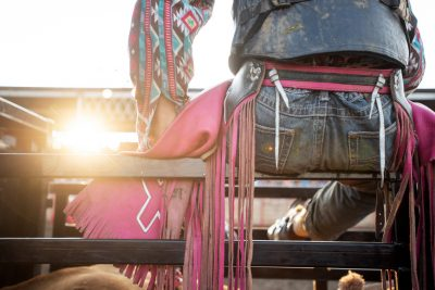 Editorial photography of a bullrider sitting on gate at rochester mn rodeo