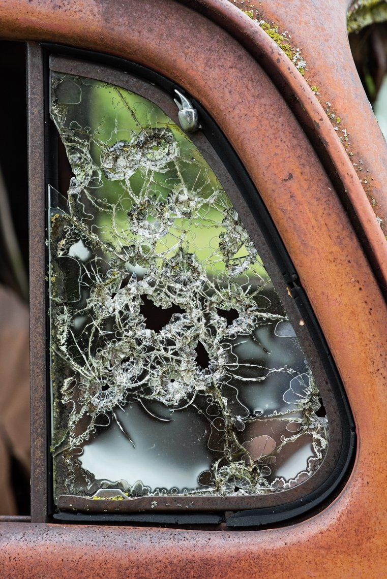 window of rusted Ford F1 with bb shot marks