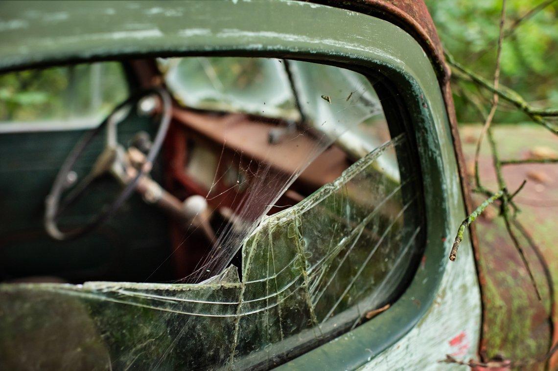 cobweb in broken window of abandoned car