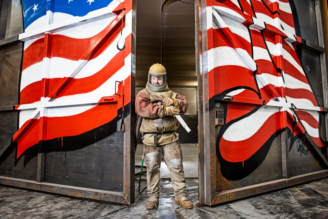 A worker at Central Sandblasting stands in the door painted with the American flag