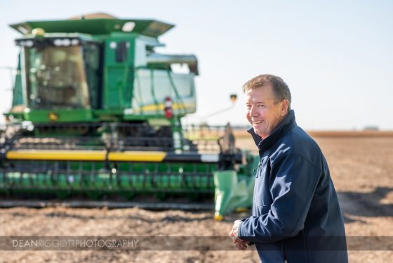 A farmer smiles in front of his combine.
