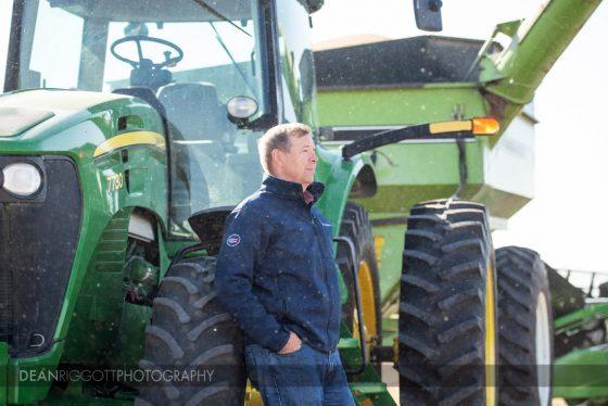 A farmer leans against his tractor